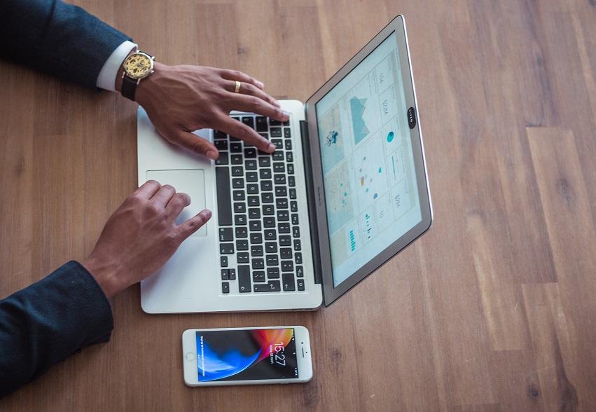 Un homme regardant un ordinateur avec un tableau de bord BI